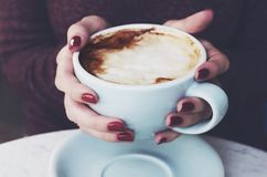 Cup of coffee with milk foam in woman`s hands Royalty Free Stock Photo