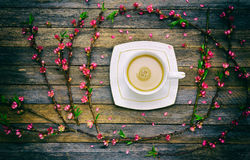 Cup of coffee with milk and a frame of peach branches with pink flowers on wooden background from barn boards Royalty Free Stock Photos