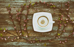Cup of coffee milk and a frame of peach branches with pink flowers on wooden background from barn boards Stock Photo