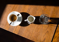A cup of coffee, milk and a glass of water. On a wooden table Royalty Free Stock Photos