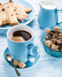 Cup of coffee, milk jug, cane sugar cubes and fruit-cake. Royalty Free Stock Photo