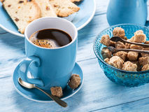 Cup of coffee, milk jug, cane sugar cubes and fruit-cake. Royalty Free Stock Image