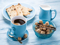 Cup of coffee, milk jug, cane sugar cubes and fruit-cake. Royalty Free Stock Photography