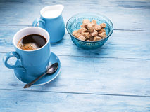 Cup of coffee, milk jug and cane sugar cubes. Stock Photos