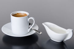 A cup of coffee with a milk jug Stock Photos