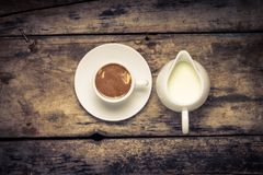 Cup of Coffee with Milk Jug on Wood Background. Warm color toned Stock Photography