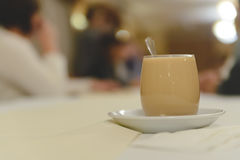 A cup of coffee with milk. At a long table royalty free stock image