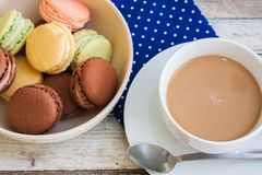 Cup of coffee with milk and macarons, closeup Royalty Free Stock Photo