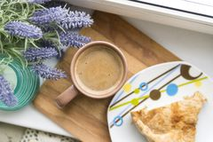 Cup of coffee with milk, a piece of cake on a plate. blue lavender branch stock photos