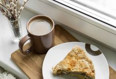 Cup of coffee with milk, a piece of cake, willow branch stock image