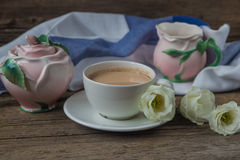 Cup of coffee with milk, red grapes, pink crockery and eustomas. On wooden table Royalty Free Stock Photo