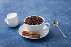 Cup of coffee milk seeds spoon cinnamon anis. Cup of coffee with seeds, milk in a white milk jug, spoon, cinnamon and anis on blue background. Horizontal Stock Images