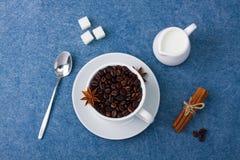 Cup of coffee milk sugar spoon cinnamon anis. Cup of coffee with seeds, milk in a white milk jug, sugar, spoon, cinnamon and anis on blue background. Top view Royalty Free Stock Photo