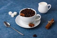 Cup of coffee milk sugar spoon cinnamon anis. Cup of coffee with seeds, milk in a white milk jug, sugar, spoon, cinnamon and anis on blue background. Horizontal Stock Photo