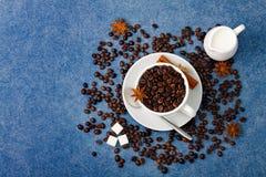 Cup of coffee milk sugar spoon cinnamon anis. Cup of coffee with seeds, milk in a white milk jug, sugar, spoon, cinnamon and anis on blue background. Horizontal Royalty Free Stock Images