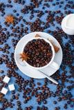 Cup of coffee milk sugar spoon cinnamon anis. Cup of coffee with seeds, milk in a white milk jug, sugar, spoon, cinnamon and anis on blue background. Vertical Royalty Free Stock Photos