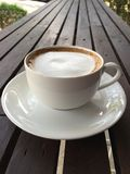 Cup of coffee with milk on wood table. In garden royalty free stock photo