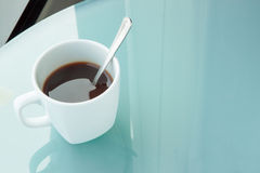 Cup of coffee on a mirror table,office. Cup of coffee on a mirror table Royalty Free Stock Photos