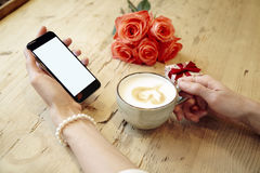 Cup of coffee and mobile phone in beautiful woman hands. Blank screen for layout. Red roses flowers behind on wooden table. St. Va Stock Image