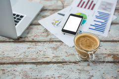 Cup of coffee with mobile phone, graph and laptop Stock Images
