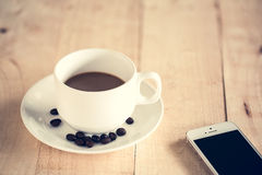 Cup of coffee with a mobile - vintage style. Royalty Free Stock Photo