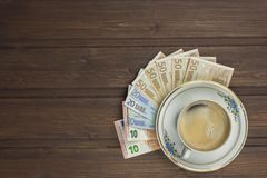 Cup of coffee and money. Valid banknotes on a wooden table Stock Photography