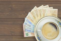 Cup of coffee and money. Valid banknotes on a wooden table Stock Photo