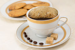 Cup of coffee with more cream and biscuits on background Royalty Free Stock Image