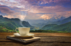 A cup of coffee. Morning cup of coffee with mountain background at sunrise Stock Photos