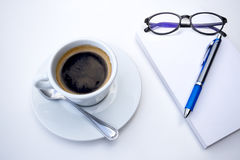 Cup of coffee in morning with pen and note book and glasses Stock Image