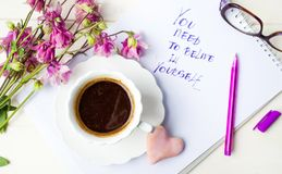 Cup of coffee on and a motivation message. With purple flowers Stock Images