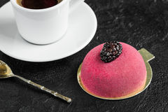 Cup of coffee with mousse cake. Beautiful cake with blackberries for dessert and a spoon on a dark background Stock Image