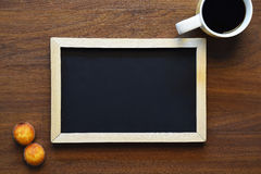 Cup of coffee, muffins and a chalkboard with copyspace. Stock Images