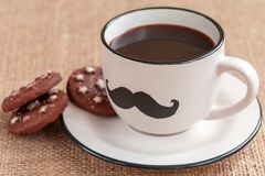 Cup of coffee with mustache on burlap background. movember. Cup of coffee with mustache and cookies. November concept. Prostate Cancer and men`s health awareness royalty free stock images