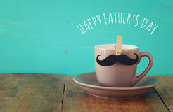 Cup of coffee with mustache. Father& x27;s day concept. Cup of coffee with mustache on wooden table. Father& x27;s day concept stock photo