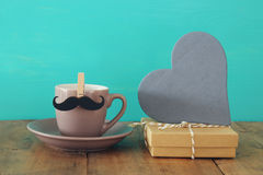 Cup of coffee with mustache next to gift box and wooden heart. Father& x27;s day concept Stock Images
