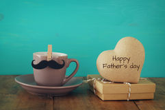 Cup of coffee with mustache next to wooden heart on the table Royalty Free Stock Images