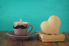 Cup of coffee with mustache next to wooden heart on the table Stock Photo