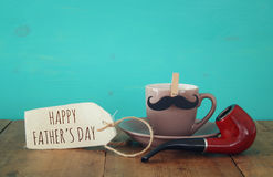 Cup of coffee with mustache and smoking pipe. Father& x27;s day conce. Cup of coffee with mustache and smoking pipe on wooden table. Father& x27;s day Royalty Free Stock Photography