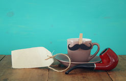 Cup of coffee with mustache and smoking pipe. Father& x27;s day conce. Cup of coffee with mustache and smoking pipe on wooden table. Father& x27;s day Stock Photography