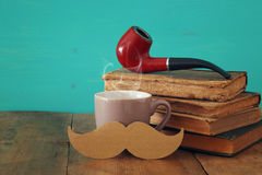 Cup of coffee with mustache and smoking pipe. Father& x27;s day concept Stock Photos