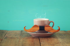 Cup of coffee with mustache on wooden table. Father& x27;s day concep Royalty Free Stock Photos