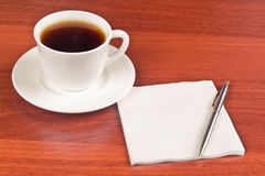 Cup of coffee and napkin Stock Photos
