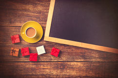 Cup of coffee near gift and blackboard Stock Images
