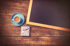 Cup of coffee near gift and blackboard Royalty Free Stock Images