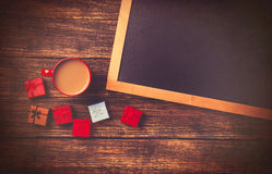 Cup of coffee near gift and blackboard Royalty Free Stock Photos