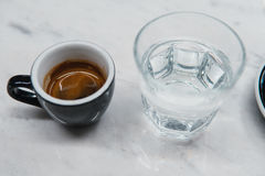Cup with coffee near a glass of water Stock Photos