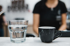 Cup with coffee near a glass of water Royalty Free Stock Photography