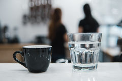 Cup with coffee near a glass of water Stock Images