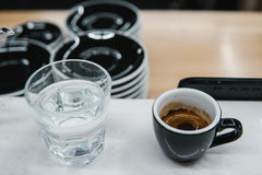 Cup with coffee near a glass of water Stock Photography